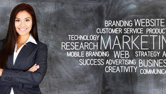 Frau steht vor Tafel mit Schlagwörtern zu Marketing